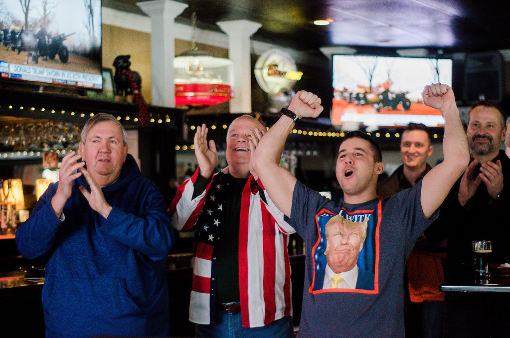 . Doug Hare, Mike Cooley and Jon Williams celebrate at Black Sheep Tavern in Sterling as they gathered to watch the inauguration of President Donald Trump on Friday morning. SENTINEL & ENTERPRISE / Ashley Green