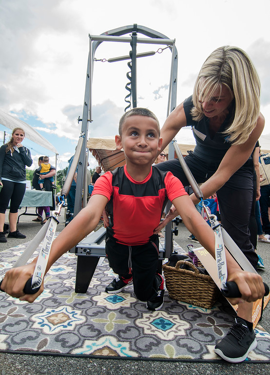 . Juelz Rosado, 9, tests his strength with the help of Kim Casto, from Bodylines Pilates during Rootsfest on Saturday, September 9, 2017. SENTINEL & ENTERPRISE / Ashley Green