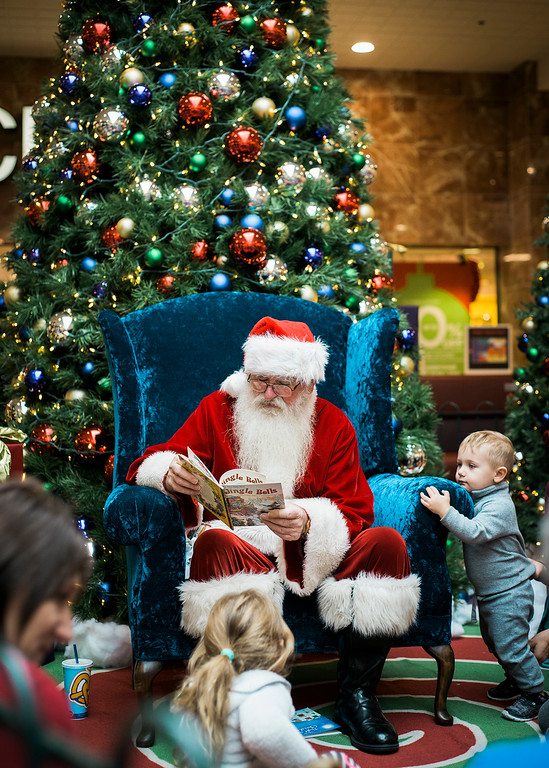 . Santa Claus, a good friend of Charlie Madden, of Sterling, reads to children during a story and craft hour at the Mall at Whitney Field on Wednesday, December 6, 2017. SENTINEL & ENTERPRISE / Ashley Green