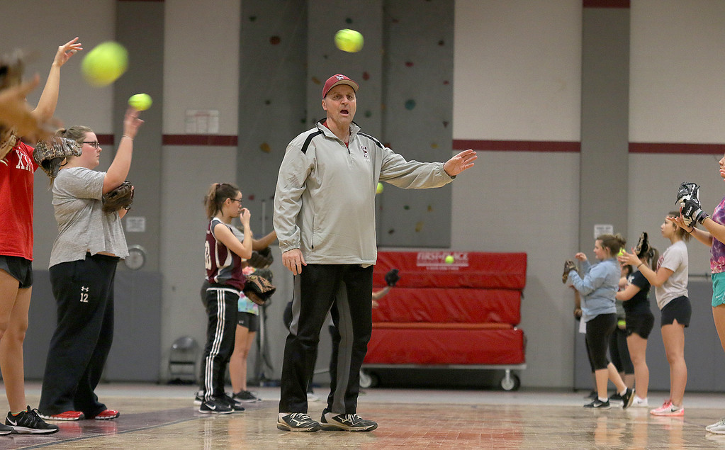 . New Fitchburg High School softball coach Mike Pelland works on throwing drills with the varsity and junior varsity team on Thursday afternoon in the gym at the high school. SENTINEL & ENTERPRISE/JOHN LOVE
