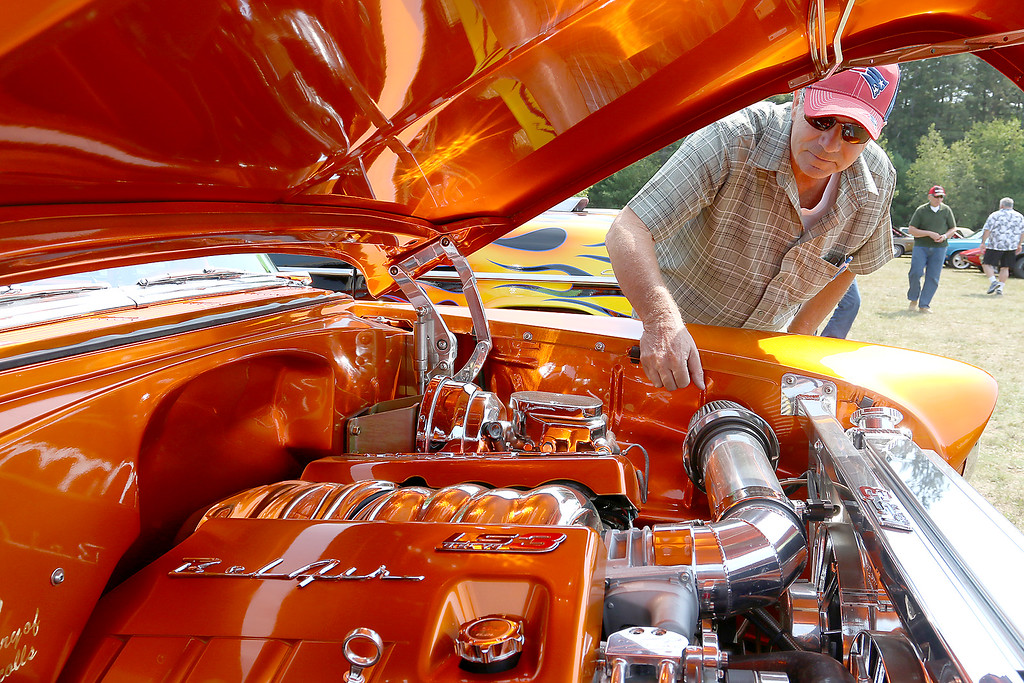 . Asbhy American Legion held its 8th annual Holmes Curran Bennett Post 361 car show fundraiser for veterans on Monday, Labor Day at Allen Field. Don Nicolls from Pelham N.H. looks over the engine of a his Chevrolet Bel-Air, that was candy orange, at the show. SENTINEL & ENTERPRISE/JOHN LOVE