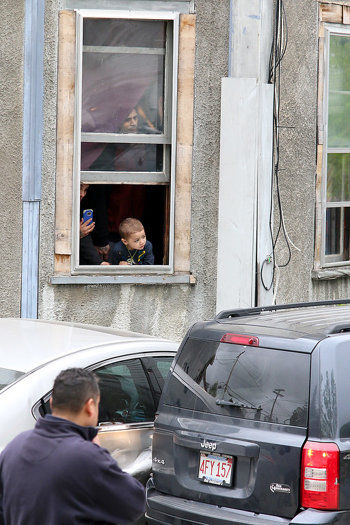 . A manwho seemed to have a medical problem veered off the road on Blossom Street in Fitchburg and hit two parked cars at 105 Blossom. Jadiel Rivera, 2 in window, and his mom Elizabeth Vazquez, on left in window, and his dad Angel Rivera just above him in window, watch everyone as they deal with the accident at next to their apartment at 105 Blossom. SENTINEL & ENTERPRISE/JOHN LOVE