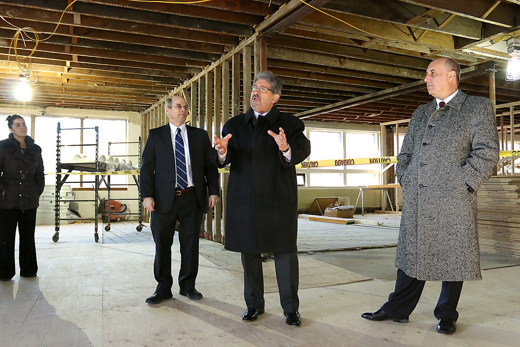 . Fitchburg State University showed off their work on the Theater Block on Main Street in Fitchburg during their phase one of the project Wednesday morning, January 31, 2018. President of FSU Richard Lapidus, right, and Executive Director of NewVue Communities for Fitchburg Marc Dohan, left,listen to Mayor Stephen DiNatale as he addresses the crowd that came to see phase one of the Theater Block. SENTINEL & ENTERPRISE/JOHN LOVE