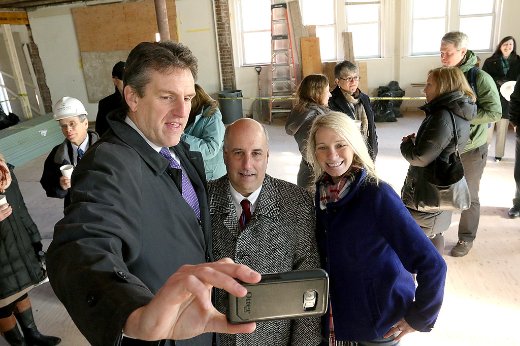 . Fitchburg State University showed off their work on the Theater Block on Main Street in Fitchburg during their phase one of the project Wednesday morning, January 31, 2018. Secretarty of Housing and Economic Development for the Commonwealth of MA Jay Ash takes a selfie with FSU President Richard Lapidus and Fitchburg City Councilor Sam Squailia during the event to showcase what FSU\'s phase one of the Theater Block looks like. SENTINEL & ENTERPRISE/JOHN LOVE