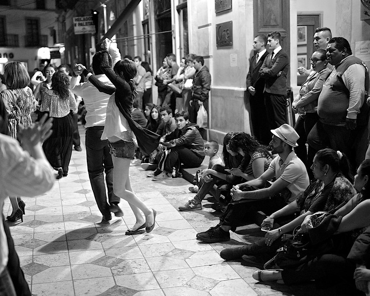 THE FIRST TIME<br /> <br /> I took this photo about a year ago – March 22, 2014, a Saturday night – while walking home through El Centro, in Guanajuato.  I like many things about this photo, but what I like best is the look on the young boy's face (middle, right, sitting on the curb) as he watches the dance. I don't know what is going through his mind, of course, but I like to think that he is seeing something so very wonderful for the first time. He won't be able to put words to it for years to come, of course, but it is an awakening, nonetheless. I like to think, too, that he never will forget the moment.