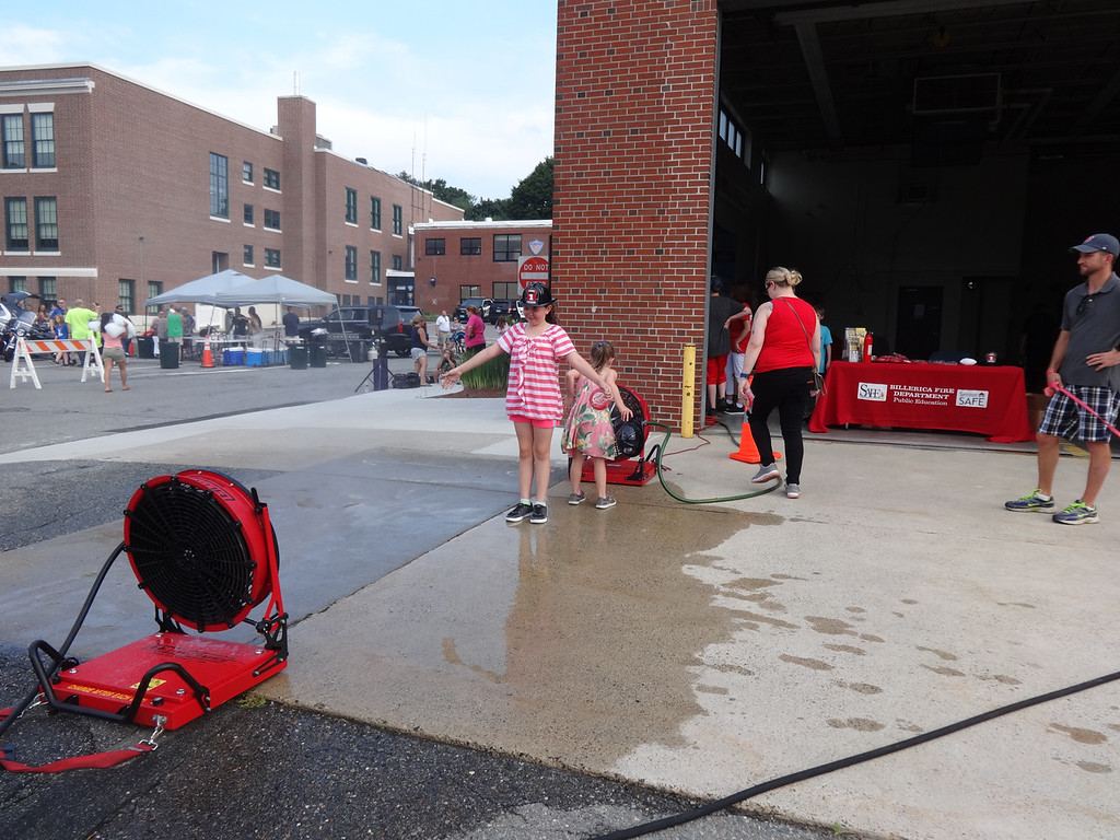 . Jordyn Morrissette, 8, of Billerica, enjoyed mist from a fan in front of the Billerica fire station, which her sister, Makayla Morrissette, 6, cooled her face. Pphoto by Mary Leach