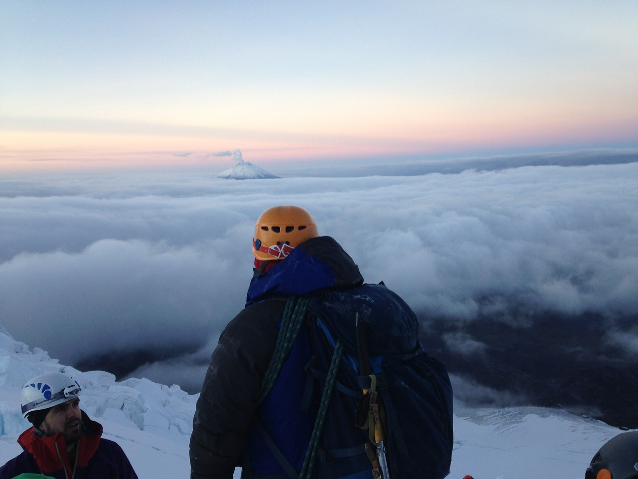 Guide Romel Sandoval pauses to watch a steaming Cotopaxi in the distance while ascending Antisana.