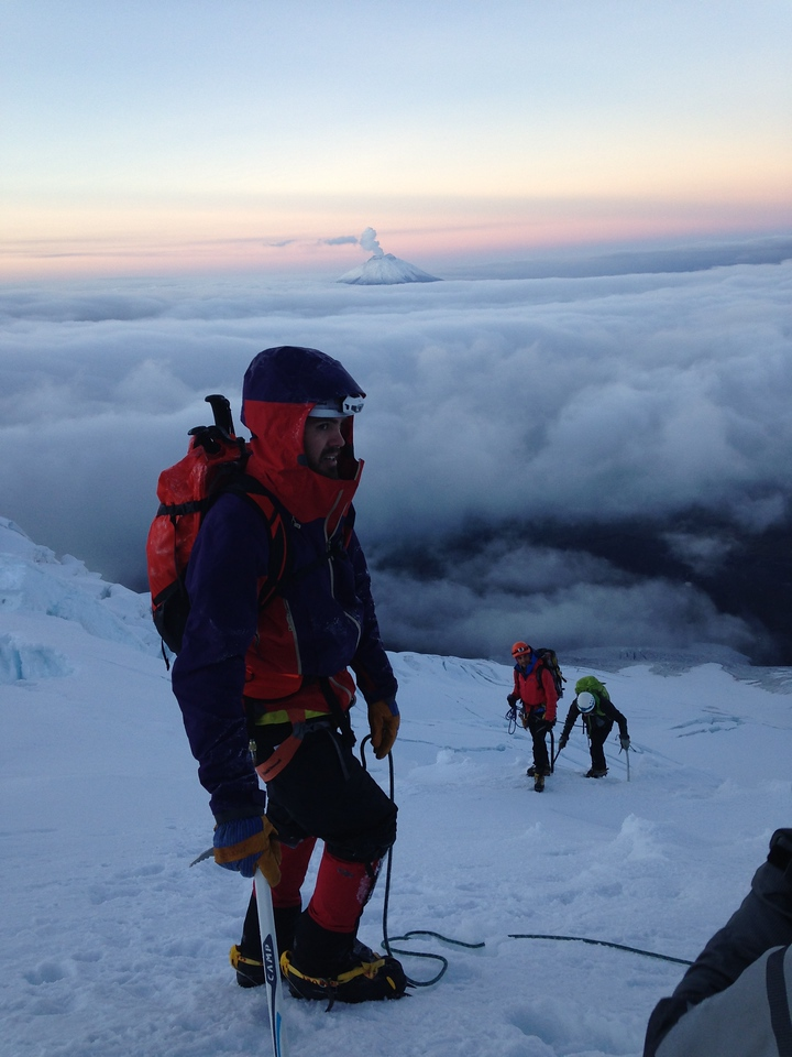 Climber Andrew pauses during a break climbing Antisana. Cotopaxi is visible in the background.