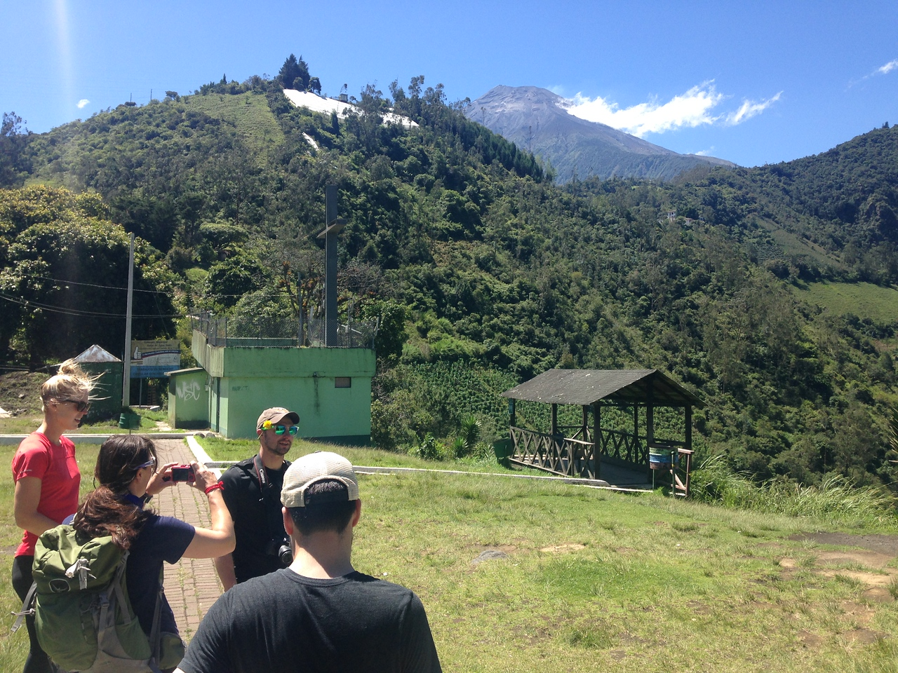 The team enjoys a break during a hiking day in Banos de Agua Santa. The very active volcano Tungurahua is in the background.