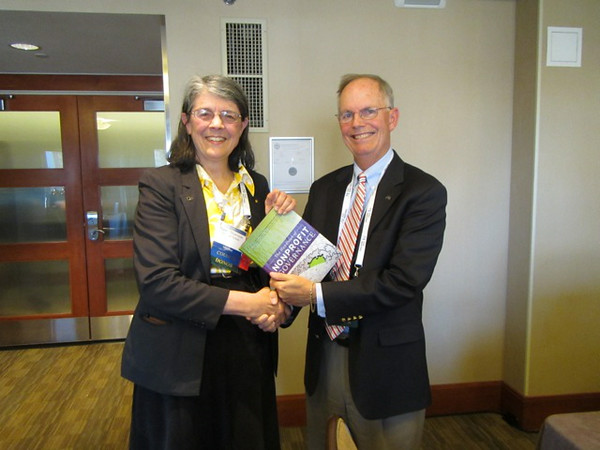 Incoming AAS Treasurer Nancy Morrison is presented a nonprofit-governance best-practices handbook by outgoing Treasurer Peter Stockman. Stockman served as Treasurer for nine years, helping to guide the Society through the transition of its journals to a new publisher and overseeing a significant increase in its net assets. Morrison is a former Councilor and a welcome addition to the current Council as Treasurer. Photo by Fritz Benedict.