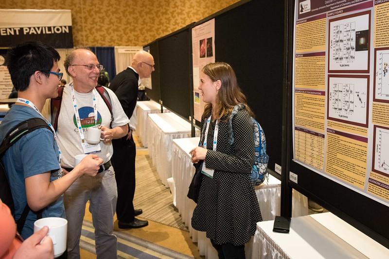 Attendees visit poster displays and exhibitors - coffee break