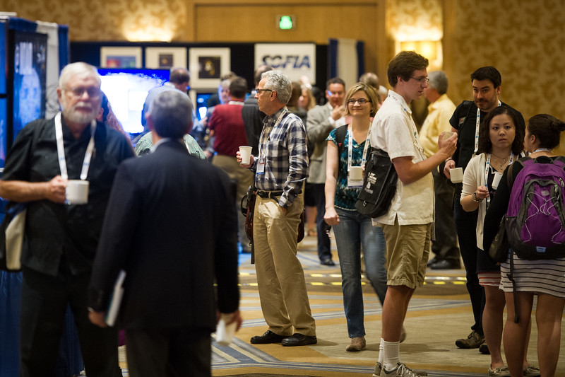 Attendees visit poster displays and exhibitors - coffee break