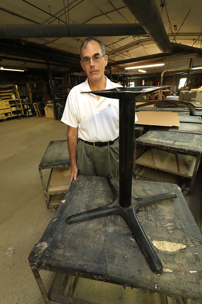 President Andy Crosby of ABCrosby & Company, Inc. stands next to a metal table support that he gets from China. SENTINEL & ENTERPRISE/JOHN LOVE