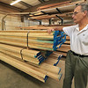 President Andy Crosby of ABCrosby & Company, Inc. stands next to some wood that he gets from Canada. SENTINEL & ENTERPRISE/JOHN LOVE