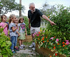 Rockport City Councilman Bill Fisher points out some tomatoes in his and his wife's garden