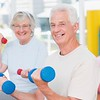 Happy senior couple lifting dumbbells in gym