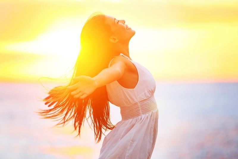 Enjoyment - free happy woman enjoying sunset. Beautiful woman in white dress embracing the golden su
