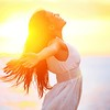 Enjoyment - free happy woman enjoying sunset. Beautiful woman in white dress embracing the golden su