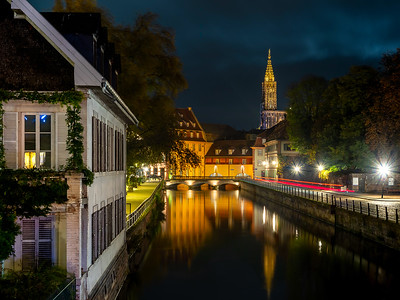 Strasbourg Cathedral view from Little France quarter. Night view with reflection in the water.