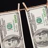 Hundred Dollar Bills Hanging From Clothesline on Dark Background
