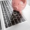 Piggy Bank Resting on Laptop Computer