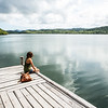 Woman sitting on a wooden dock.