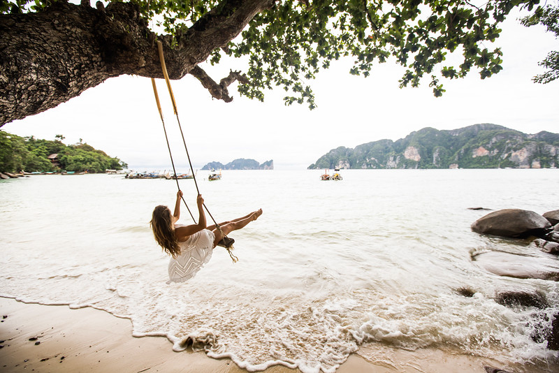 A woman on a rope swing over a beach.