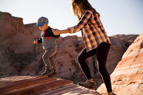 A mother and her young son hiking in the desert