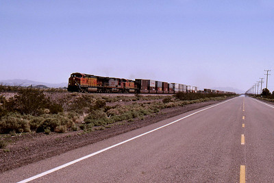 """-- 2001 -- Under a clear blue sky a """"Stack"""" train heads west across the Mojave Desert behind a trio of General Electric built Dash 9's alongside the """"Mother Road"""" at Minneola, west of Newberry Springs; bound for a crew change at Barstow."""
