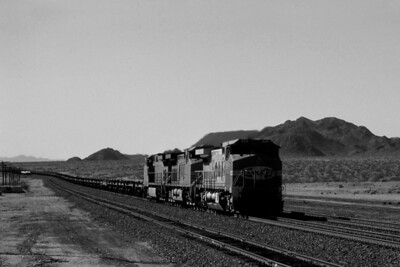"""-- 2001 -- With the Marble Mountains of the Mojave Desert in the background a long train of bare tables and spine cars head east through the siding at Bagdad led by a """"Santa Fe Warbonnet - Dash 9"""" #929 under a cloudless sky."""
