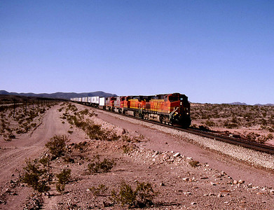 """-- 2001 -- With the dynamic brakes whining BNSF General Electric built """"Dash 9"""" #4998 leads an eastbound """"Pig Train"""" down the eastern slopes of Ash Hill at Klondike at full line speed."""
