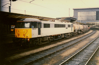 """-- 1989 -- Class 86/5 #86507, """"L.S. Lowery""""; heads south through Carlisle station leading a mixed freight. The loco was built by English Electric and entered traffic in June 1965 as #E3169 working passenger trains on the West Coast Mainline from London to the northwest and Scotland. Re-numbered to #86239 on the introduction of TOPS. Briefly re-numbered as #86507 when dedicated to freight traffic and back to #86239 on returning to passenger duties. Allocated to Rail Express Systems (RES) on it introduction in 1991. The locomotive was involved in a major accident at Stafford in 1996 that resulted in its demise. The engine hit a derailed freight train and because of the speed it was travelling at it became embedded in a end wall of a line-side house, and #86239 was scrapped twelve months later."""