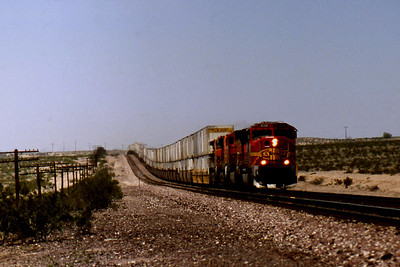 """-- 2001 -- An ex-ATSF General Motors built SD75M in """"Santa Fe Warbonnet"""" livery leads a J.B. Hunt container train east through the rolling countryside of the Mojave Desert near Lavic, on the 170 mile run across the desert between crew changes from Barstow in the west to Needles on the banks of the Colorado River in the east."""
