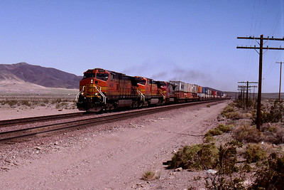 """-- 2001 -- Three General Electric  built """"Dash 9's"""" speed west away from Ludlow at Lavic with a train of double-stack containers on the race track that is Burlington Northern Santa Fe's """"Southern Transcon Main Line""""."""