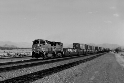 """-- 2001 -- Burlington Northern Santa Fe's (BNSF) General Electric built """"Dash 9"""" #4334 leads a sister and a train of boxes through the sidings at what remains of the town of Bagdad in the Mojave Desert. Bagdad was a watering point in steam days with station buildings and a diner, but was abandoned in the late 1950's when diesel power took over. The cemetery can still be seen on the far side of the tracks, but the palm tree that stood here for many years has long since gone - cut down by vandals!  In the distance can be seen a Distributed Power Unit (DPU) at the rear of the train."""