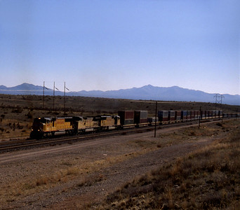 """-- 2003 -- With the sun climbing higher in the sky and nothing moving for just over an hour until a westbound """"Double Stack"""" service slowly creeps into view as it climbs away from the San Pedro River Valley and the town of Benson as it heads towards the summit at Mescal led by Union Pacific's GM-EMD bulit SD70M #4439. (0702)"""