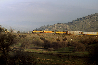 -- 2001 -- With the early morning mist slowly clearing three big Union Pacific (UP) GE's inch their way round the spiral at Tehachapi Loop leading an eastbound rake of empty auto-racks.