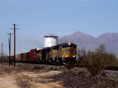 """-- 2003 --  An eastbound """"Mixed Freight"""" races towards Tucson led by Union Pacific's (UP) General Electric built SD70M #4711 passes the steam age water tower at Red Rock. (0706)"""
