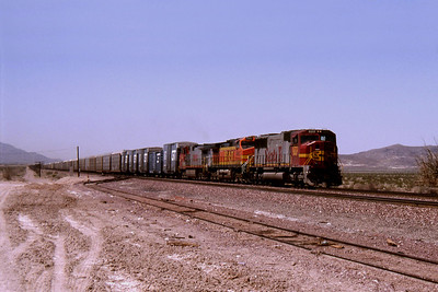 """-- 2001 -- A train of mainly empty auto-racks passes the siding at Hector heading east across the barren landscape that is the Mojave Desert led by """"Santa Fe Warbonnet"""" #8213, a GM-EMD built SD75M dating from 1995."""