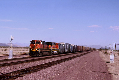 """-- 2001 -- Approaching a searchlight signal is a pair of """"Dash 9's"""" in """"Heritage 1"""" paint led by #1016 wheeling a mixed freight west across the Mojave Desert at Bagdad. Bagdad is reputed to be the second driest place in the USA, after Death Valley in Eastern California; with NO rain falling for up to three years at a time."""