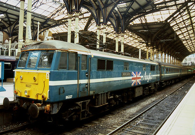 """-- 2004 -- An Anglia service to Norwich waits to depart London Liverpool Street with Class 86/2 #86227, """"Golden Jubilee""""; complete with """"Union Jack"""" propelling the train. The locomotive was withdrawn from service seven months later and cut up at Booths in Rotherham in July 2005."""