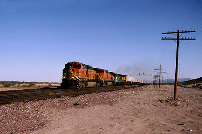 """-- 2001 -- A westbound """"Pig Train"""" breasts Ash Hill at Squaw Summit, 1944 feet above sea level; passing the wye, used for stabling a helper set; behind some of BNSF's mixed power."""