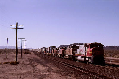 """-- 2001 -- A General Motors built SD75M in """"BNSF Warbonnet"""" livery #8280 speeds east off of Ash Hill on the Needles Subdivision with a long container train at western end of the siding at Bagdad. Note the sun shade on the cab side windows essential equipment in this part of the world."""