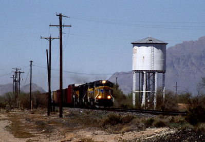 """-- 2003 --  An eastbound """"Mixed Freight"""" races towards Tucson led by Union Pacific's (UP) General Electric built SD70M #4711 passes the steam age water tower at Red Rock. (0705)"""