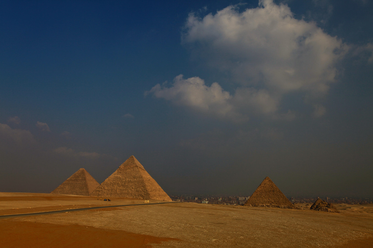 The Pyramids of Giza consist of the Great Pyramid of Giza (known as the Great Pyramid and the Pyramid of Cheops or Khufu) to the far left, the somewhat smaller Pyramid of Khafre (or Chephren) in the middle and the relatively modest-sized Pyramid of Menkaure (or Mykerinos) on the far left.  The three shorter pyramids on the right are the Queen's Pyramids.