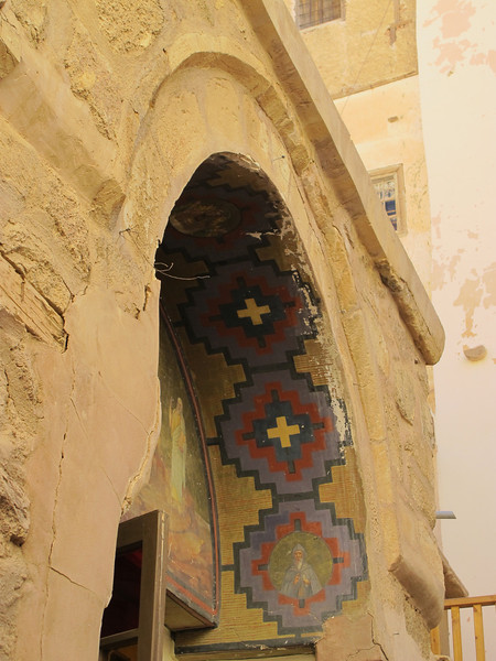 "The large four-leaved doorway at the entrance to the nave has been preserved from the sixth century. On these is carved the same verse from the Psalms that is carved over the entrance into the monastery, ""This is the gate of the Lord, into which the righteous shall enter.""  Above the door is a mosaic dating back hundreds of years."