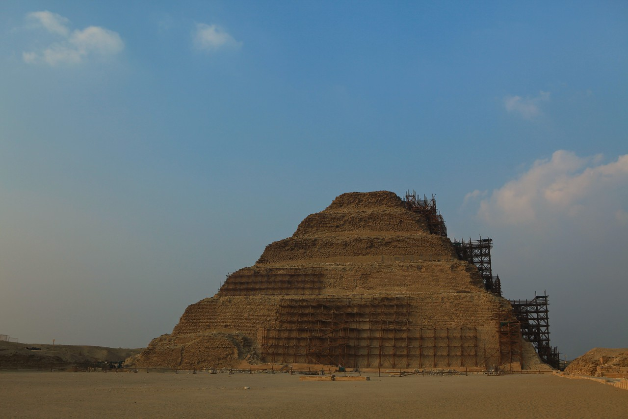 This is the Djoser Step Pyramid, which predates the Great Pyramid of Giza. Djoser is the best-known pharaoh of the Third dynasty of Egypt. He commissioned his official, Imhotep, to build the first of the pyramids, a step pyramid for him at Saqqara. Radiocarbon dating indicates that Djoser's reign began sometime between 2691 to 2625 BC