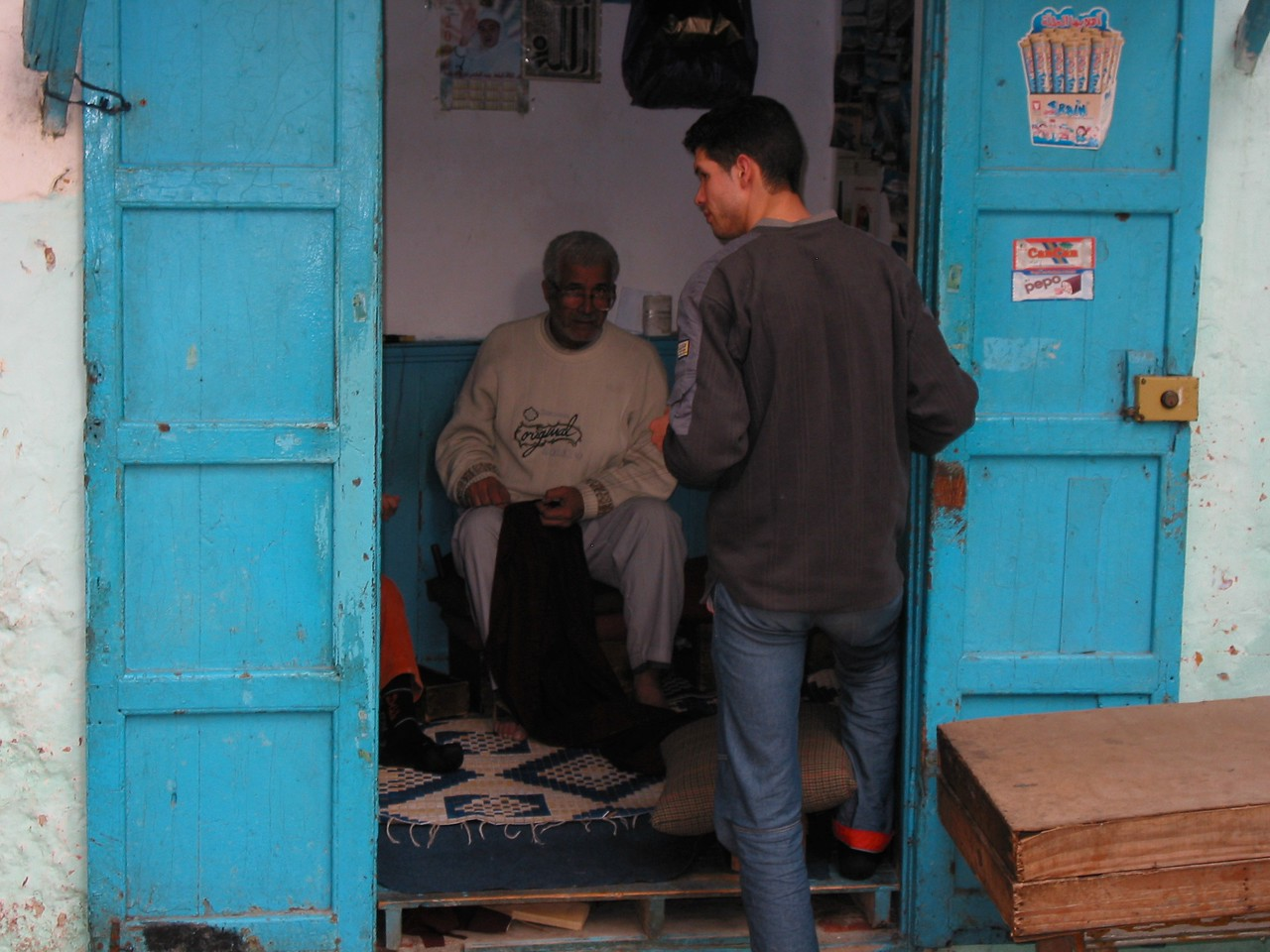 Many shops are very small.  Here a tailor works on clothing repair.