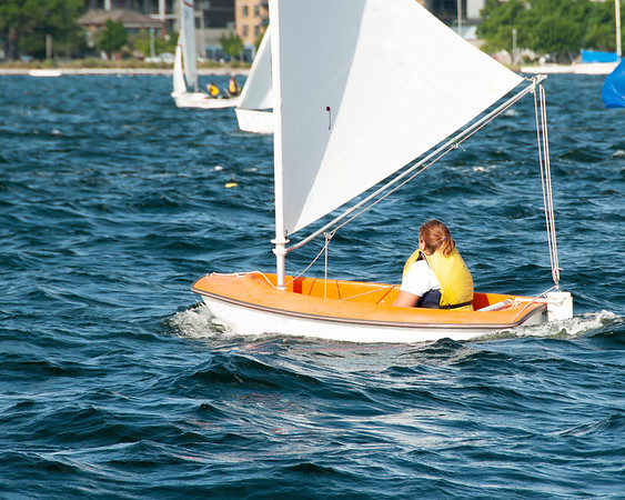 Sole female sailor Sailing small sailboat solo on an inland waterway.
