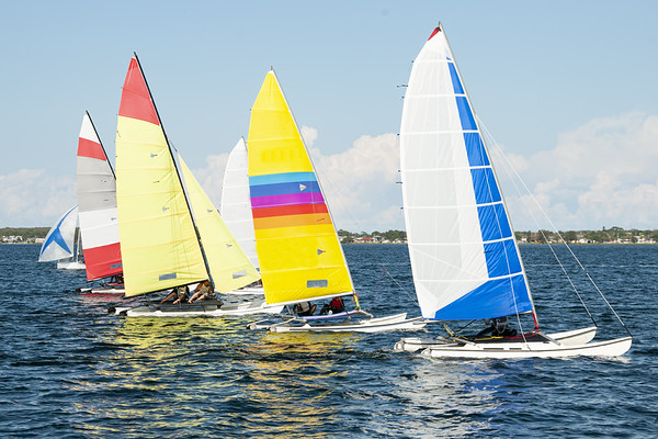 Children close sailing, racing catamarans with brightly coloured sails.
